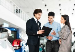 spouses-buying-car-consulting-with-dealer-guy-DX7FNUF.jpg